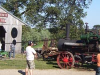 A steam engine powers the pioneer saw mill.