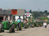 John Deere tractors lined for the parade through the Little Log House Pioneer Village.