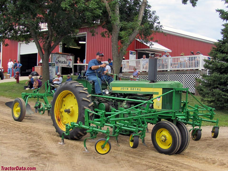 John Deere 520 with mounted cultivators and plow.