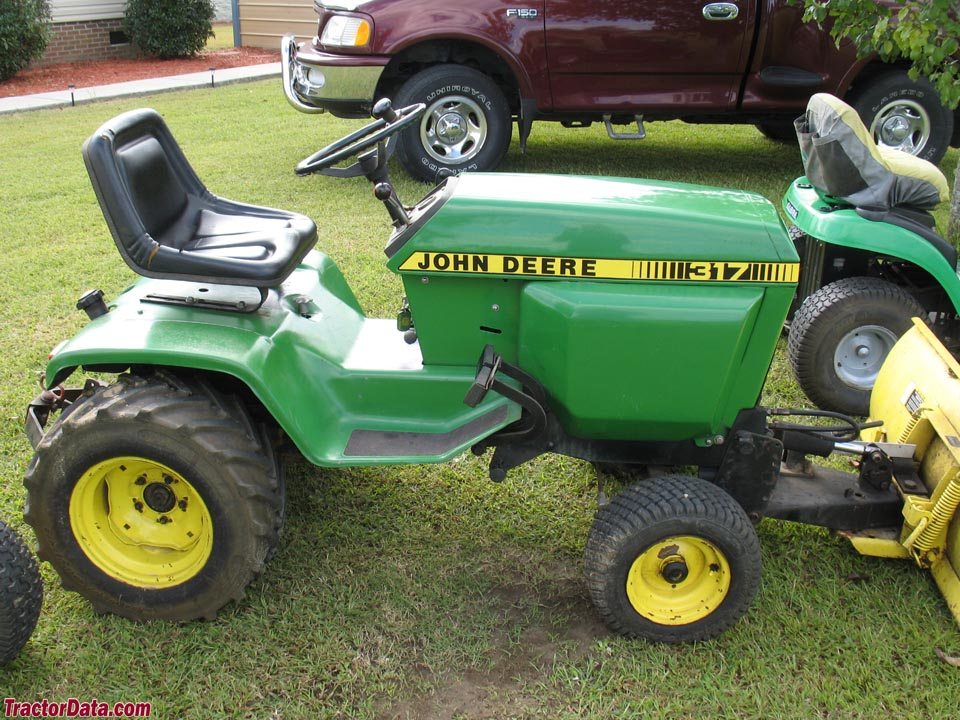 John Deere 317 with front blade and integral hitch.