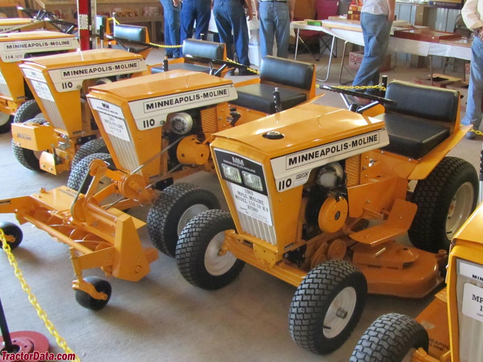 Display of three Minnapolis-Moline Town & County 110 garden tractors, with attachments.